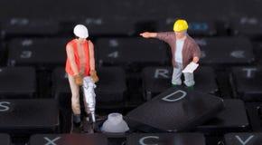 Miniaturarbeitskräfte mit dem Bohrgerät, das an Tastatur arbeitet Lizenzfreie Stockbilder