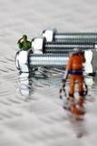 Miniaturarbeitskräfte mit Mutterbolzen Lizenzfreies Stockfoto