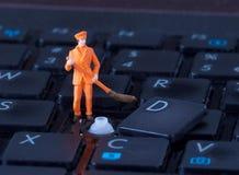 Miniaturarbeitskraft mit dem Besen, der an Tastatur arbeitet Lizenzfreies Stockfoto