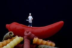 Miniaturas do cozinheiro, da massa e da pimenta de pimentão encarnado Imagem de Stock Royalty Free