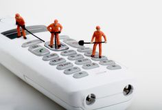 Miniaturas dos trabalhadores que fixam um telefone sem fios Fotografia de Stock Royalty Free