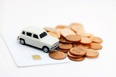 Miniaturautomodell auf Kreditkarte mit Münzen Konzept des Geldes, Stockbilder
