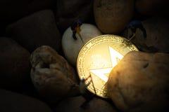 Miniaturbergmänner, die goldene Moreno-Münze im Bergwerk graben lizenzfreies stockfoto