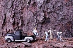 Miniaturchef, der auf dem aufpassenden Arbeitskraftarbeiten des Fahrzeugs sitzt lizenzfreies stockbild