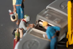 Miniature Artisans Doing Maintenance. A group of tiny miniature artisans working together to repair a cable connection in a teamwork concept Stock Photos