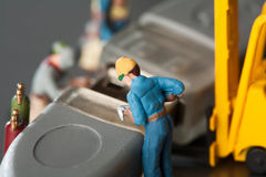 Miniature Artisans Doing Maintenance. A group of tiny miniature artisans working together to repair a cable connection in a teamwork concept Royalty Free Stock Images