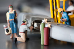 Miniature Artisans Doing Maintenance. A group of tiny miniature artisans working together to repair a cable connection in a teamwork concept Stock Images