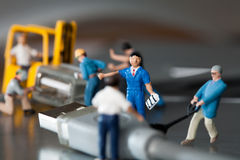 Miniature Artisans Doing Maintenance. Teamwork In The Workplace. A team of miniature toy model artisans repairs data cables Stock Images