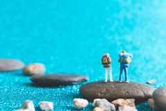 Miniature Backpacker on blue glitter background. Miniature Backpacker , Tourist people on blue glitter background Royalty Free Stock Image
