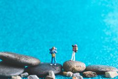 Miniature Backpacker on blue glitter background. Miniature Backpacker , Tourist people on blue glitter background Royalty Free Stock Photo