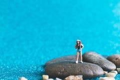 Miniature Backpacker on blue glitter background. Miniature Backpacker , Tourist people on blue glitter background Stock Photos