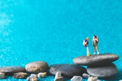 Miniature Backpacker on blue glitter background. Miniature Backpacker , Tourist people on blue glitter background Stock Images