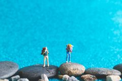 Miniature Backpacker on blue glitter background. Miniature Backpacker , Tourist people on blue glitter background Royalty Free Stock Photography
