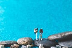 Miniature Backpacker on blue glitter background. Miniature Backpacker , Tourist people on blue glitter background Stock Photo