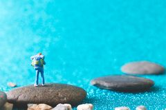 Miniature Backpacker on blue glitter background. Miniature Backpacker , Tourist people on blue glitter background Stock Photography