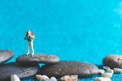 Miniature Backpacker on blue glitter background. Miniature Backpacker , Tourist people on blue glitter background Stock Image