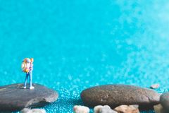 Miniature Backpacker on blue glitter background. Miniature Backpacker , Tourist people on blue glitter background Royalty Free Stock Images