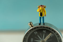 Miniature backpackers standing on compass as background travel c Royalty Free Stock Images