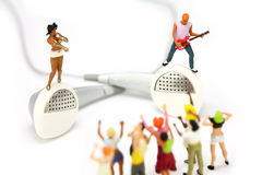 Miniature band on a pair of ear buds. MP3 concept. Stock Images