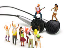 Miniature band on a pair of ear buds. MP3 concept. Royalty Free Stock Image