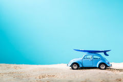 Miniature blue car with surfboard. On a bright blue background stock photography