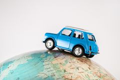 NIS, SERBIA - JANUARY 8 2018 Miniature figure toy car Mini Morris on geographical globe of earth on white background in studio. Miniature blue figure toy car Stock Image