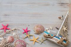 Miniature boat, starfishes, seashells and fishing net on a grey background. Time of sailing. royalty free stock images