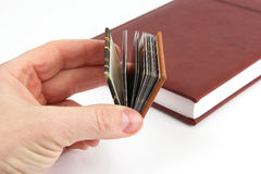 Miniature book in hand on a background of the usual books Stock Photos