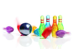 Miniature bowling action. Miniature bowling pins hit by a ball. Motion blur shows the pins falling stock image
