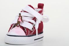 Miniature of a boy sitting on a sneaker Stock Images