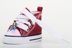 Miniature of a boy sitting on a sneaker Royalty Free Stock Images