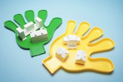 Miniature Building Models on Plastic Hands. On Blue Background stock photos