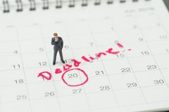 Miniature business man standing on desktop calendar with red circle on important date with handwriting deadline, goal or target. Date of work project plan stock images