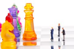 Miniature business people with colorful glass chess,. Business concept Stock Photos