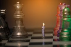 Miniature business people with colorful glass chess,. Business concept Stock Image