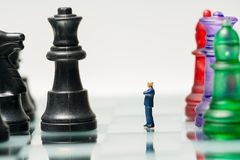Miniature business people with colorful glass chess,. Business concept Royalty Free Stock Image