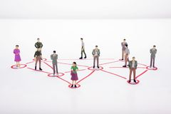 Miniature business people in conection scheme over white backdro. P or background Royalty Free Stock Photo