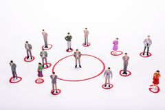 Miniature business people in conection scheme over white backdro. P or background Stock Photography