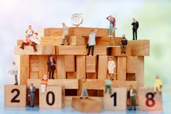 Miniature business people sitting on wood block with number 2018, Royalty Free Stock Photos