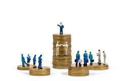 Miniature business people on stacks of coins Royalty Free Stock Image