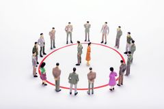 Miniature business people standing in circle over backdrop or ba. Ckground Royalty Free Stock Photo