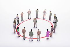 Miniature business people standing in circle over backdrop or ba. Ckground Stock Image