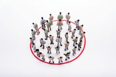 Miniature business people standing in circle over backdrop. Or background Stock Images
