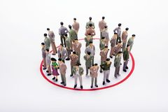 Miniature business people standing in circle over backdrop or ba. Ckground Royalty Free Stock Image