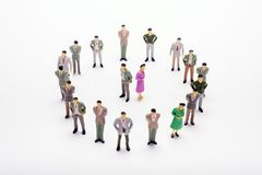 Miniature business people standing in circle over backdrop. Or background Royalty Free Stock Photography