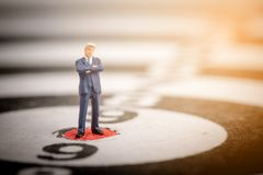 Miniature business people standing on dartboard Stock Photo