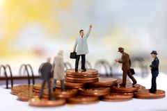 Miniature business people standing on step of coin money. Finance, investment and growth in business concept. Stock Image