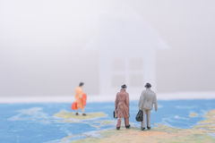 Miniature business people travel going home on world map. Royalty Free Stock Image