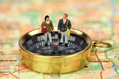Miniature business travelers on a compass. Miniature business travelers holding luggage and standing on a compass. The compass is on a map. Business travel Royalty Free Stock Photos