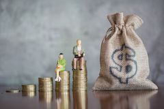 Miniature businessman and coins, Money saving, business investment royalty free stock images
